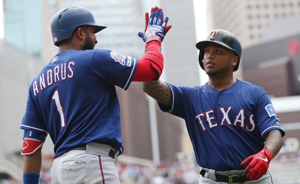 Texas Rangers' Elvis Andrus, left, high-fives Willie Calhoun on his two-run home run off Minnesota Twins relief pitcher Tyler Duffey in the sixth inning of a baseball game Saturday, July 6, 2019, in Minneapolis. (AP Photo/Jim Mone)