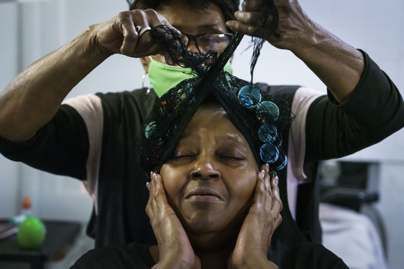 Earnestine Tarrant styles the hair of Altha Hearne at her hair salon in South Dallas on her final day working before her retirement, Thursday, Dec. 31, 2020. Tarrant opened her beauty salon in a tiny house on a corner in 1979. After four decades in business, she decided to close on New Year's Eve.