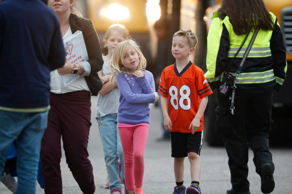 Students followed their teacher off a bus and into a recreation center where they were reunited with their parents after a shooting at a suburban Denver middle school Tuesday, May 7, 2019, in Highlands Ranch, Colo.