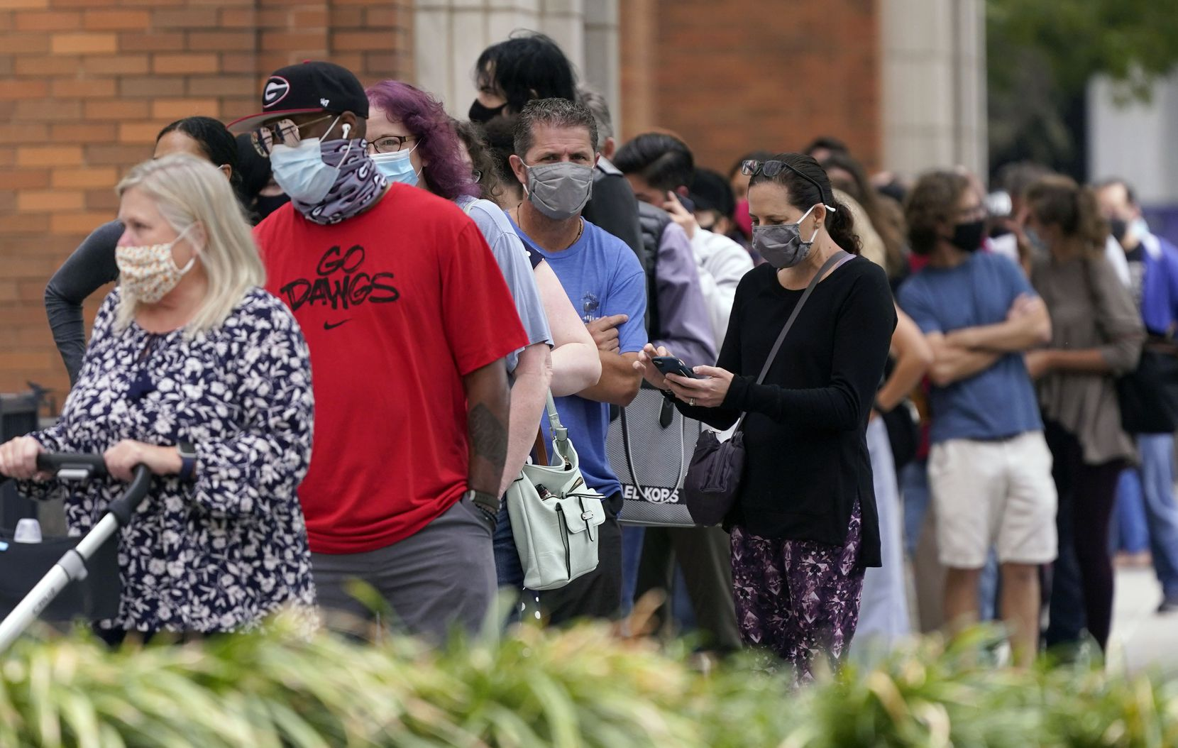 Voters wait to cast ballots at the American Airlines Center during early voting Thursday, Oct. 15, 2020, in Dallas. (AP Photo/LM Otero)