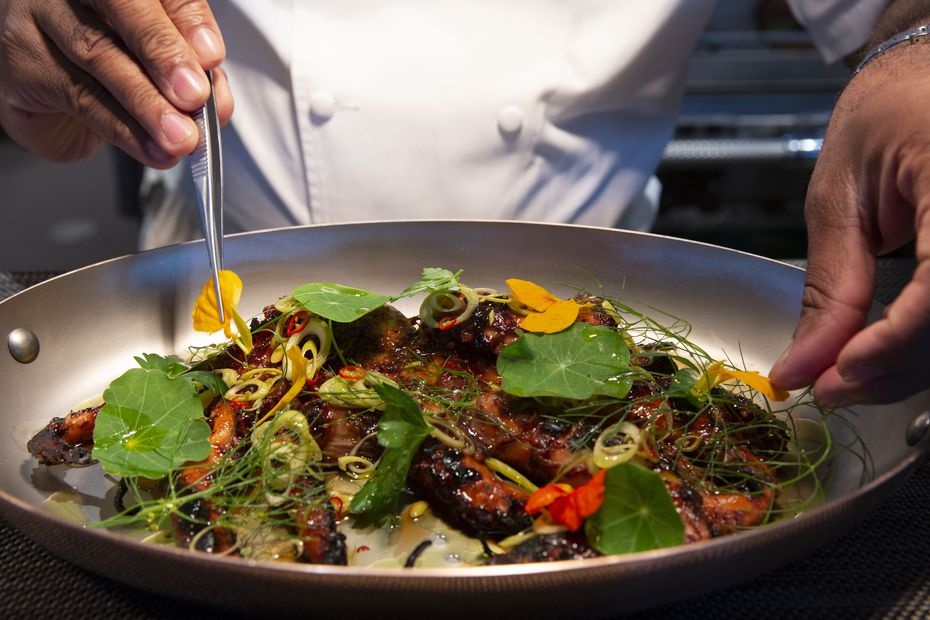 Chef Nilton 'Junior' Borges puts the final touches on a grilled octopus dish at Meridian.