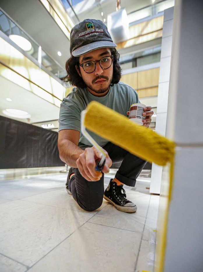 """Artist Drigo, Eric Rodriguez, paints his sculpture """"Growing Up' at the Galleria in Dallas. His murals are also visible at The Hill on the northeast corner of Walnut Hill and N. Central Expressway. (Brandon Wade/Special Contributor)"""