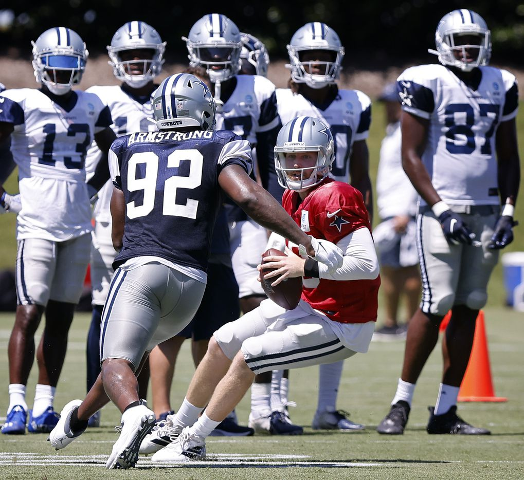 Dallas Cowboys quarterback Cooper Rush (10) tries to elude defensive end Dorance Armstrong (92) as he looks for a receiver during Training Camp practice at The Star in Frisco, Texas, Tuesday, August 24, 2021.(Tom Fox/The Dallas Morning News)