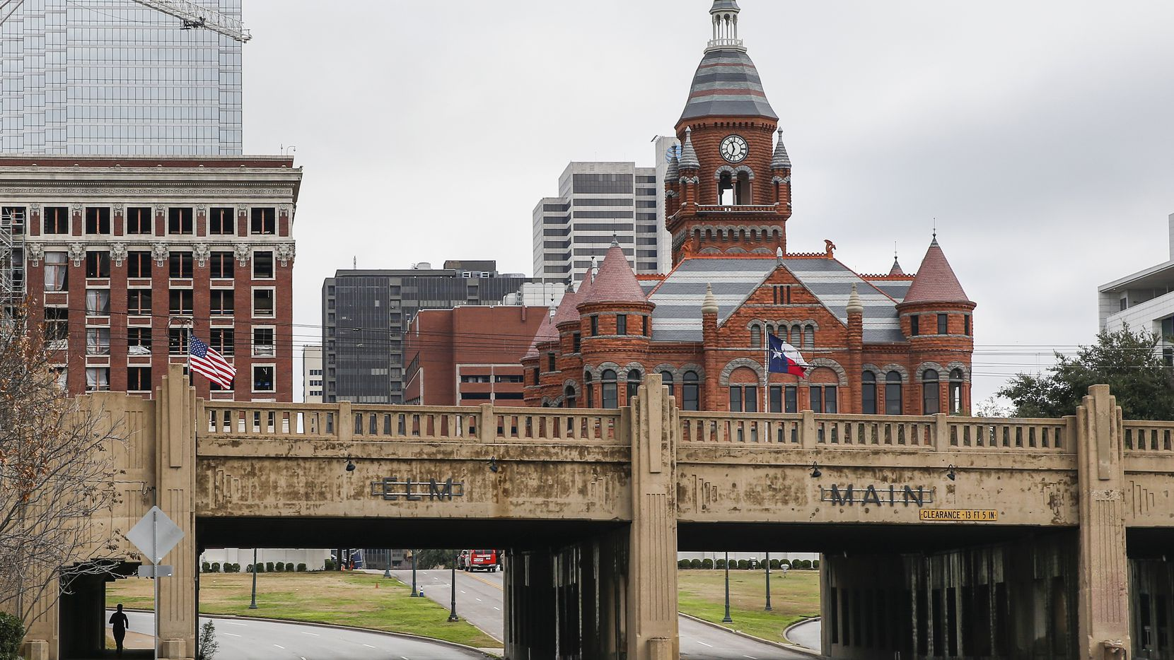A jogger (far left) passes by Martyrs Park (left) on Thursday, Jan. 23, 2020 in Dallas. At right is the Triple Underpass, and behind it is Dealey Plaza.