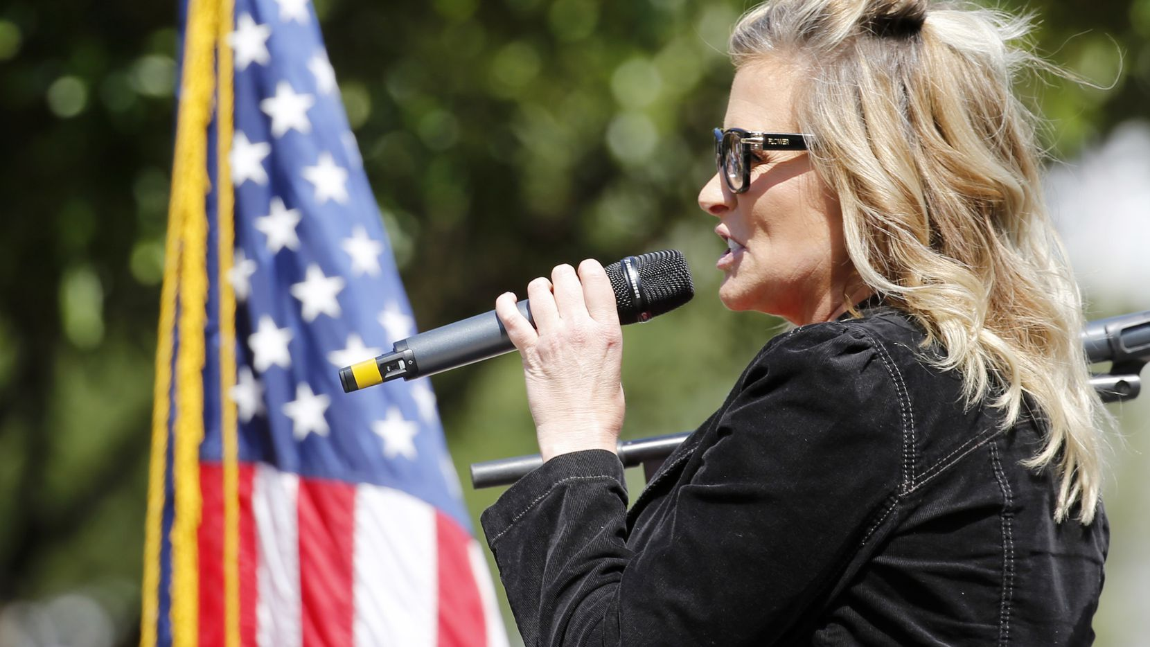 Business owner Shelley Luther addresses the crowd during an Open Texas rally outside Frisco City Hall.
