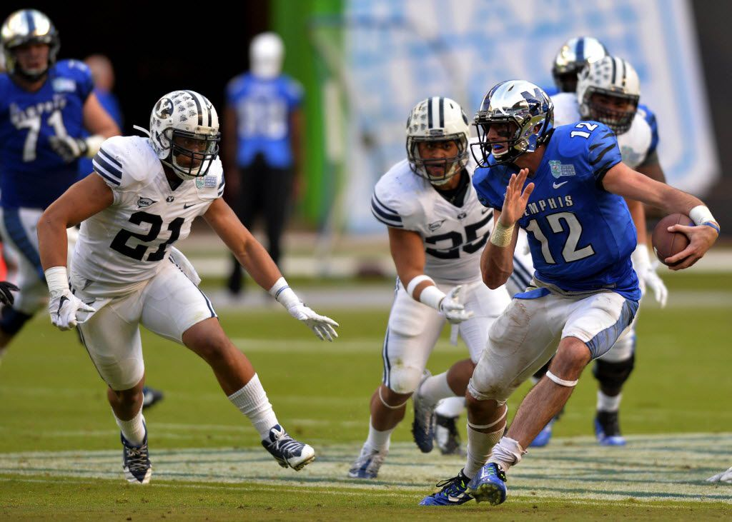 Dec 22, 2014; Miami, FL, USA; Memphis Tigers quarterback Paxton Lynch (12) scrambles away from Brigham Young Cougars running back Jamaal Williams (21) during the third quarter in the Miami Beach Bowl at Marlins Park. Memphis won 55-48 in a double overtime. Mandatory Credit: Steve Mitchell-USA TODAY Sports ORG XMIT: USATSI-211976