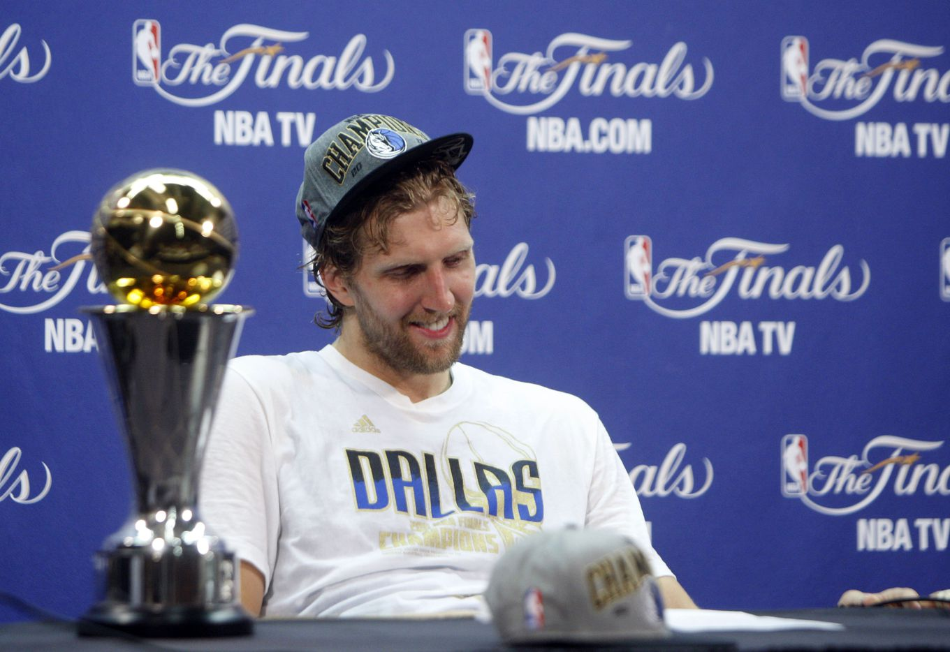 Dallas Mavericks power forward Dirk Nowitzki (41) smiles during an interview after winning in game six of the NBA Finals between the Miami Heat and the Dallas Mavericks at the American Airlines Arena in Miami, Florida, June 12, 2011. The Mavericks won 105-95 to take the title. (Vernon Bryant/The Dallas Morning News) Next to him is the Bill Russell NBA Finals MVP trophy