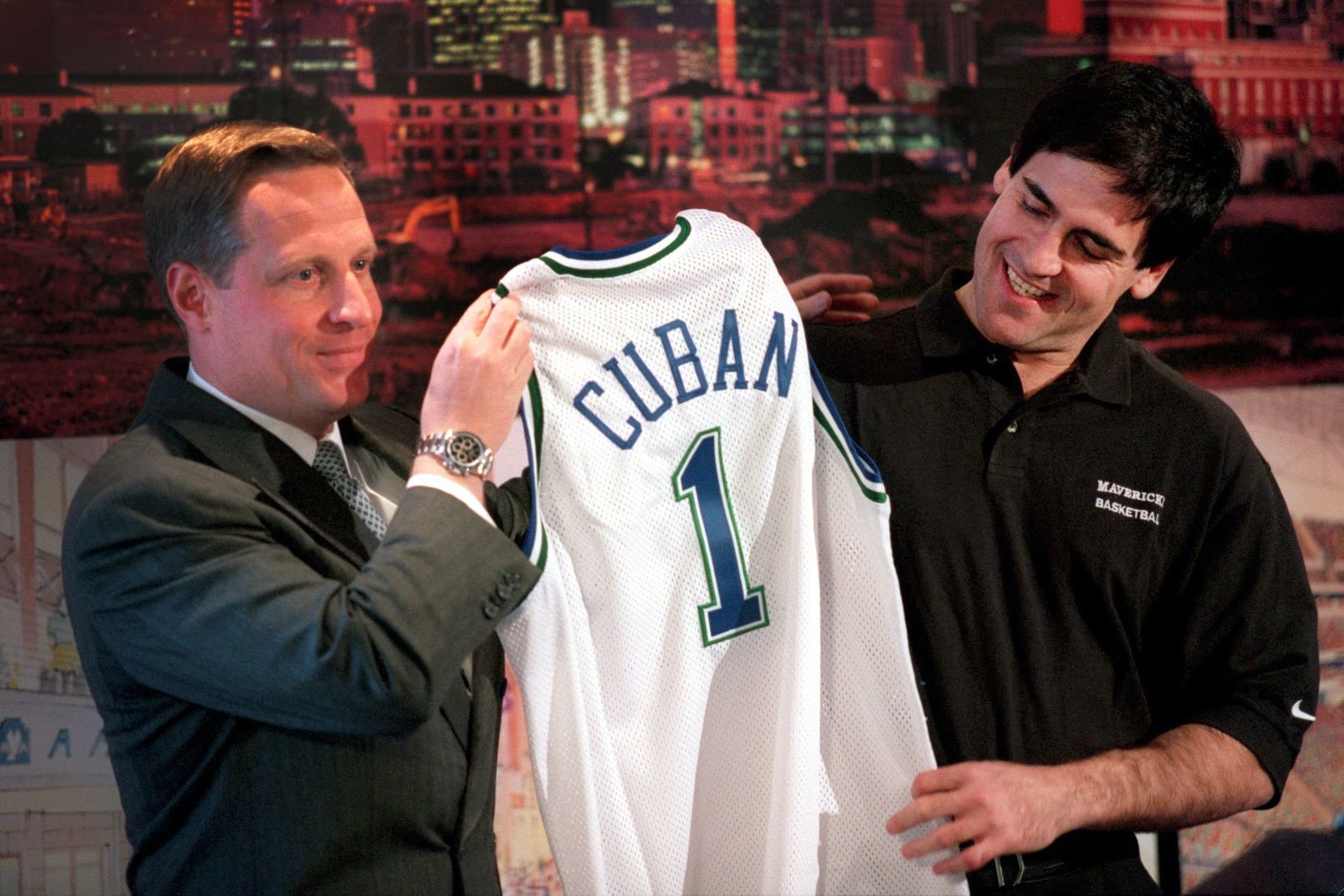 January 20, 2000: Ross Perot Jr. (left) presents Mark Cuban with a Dallas Mavericks jersey during a press conference to formally announce their definitive agreement for the sale of the Dallas Mavericks. Cuban agreed to purchase the franchise for $285 million on Jan. 4, 2000.