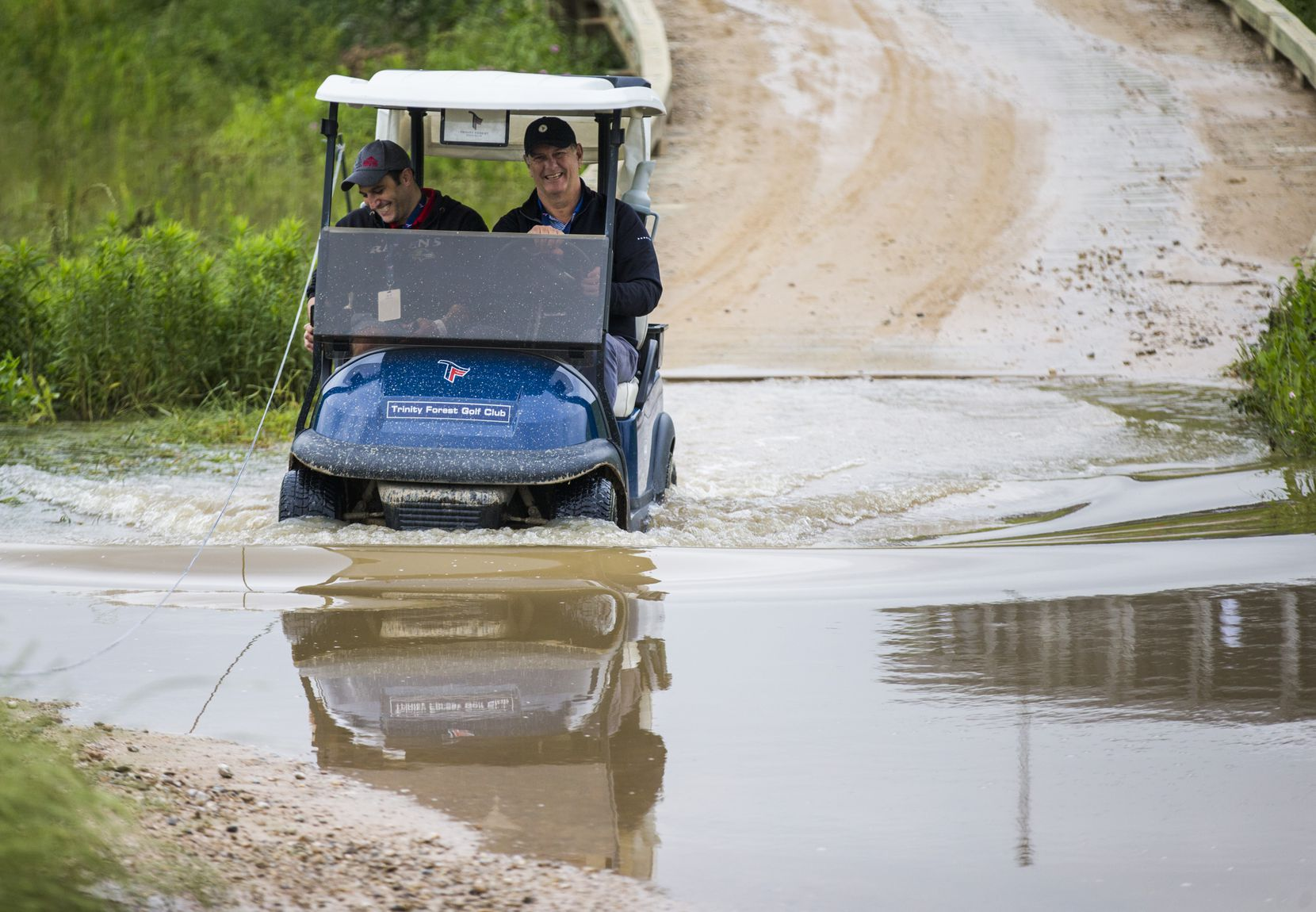 Mayor Mike Rawlings drives a golf cart through a large puddle near hole 12 during round 3 of the AT&T Byron Nelson golf tournament on Saturday, May 11, 2019 at Trinity Forest Golf Club in Dallas. (
