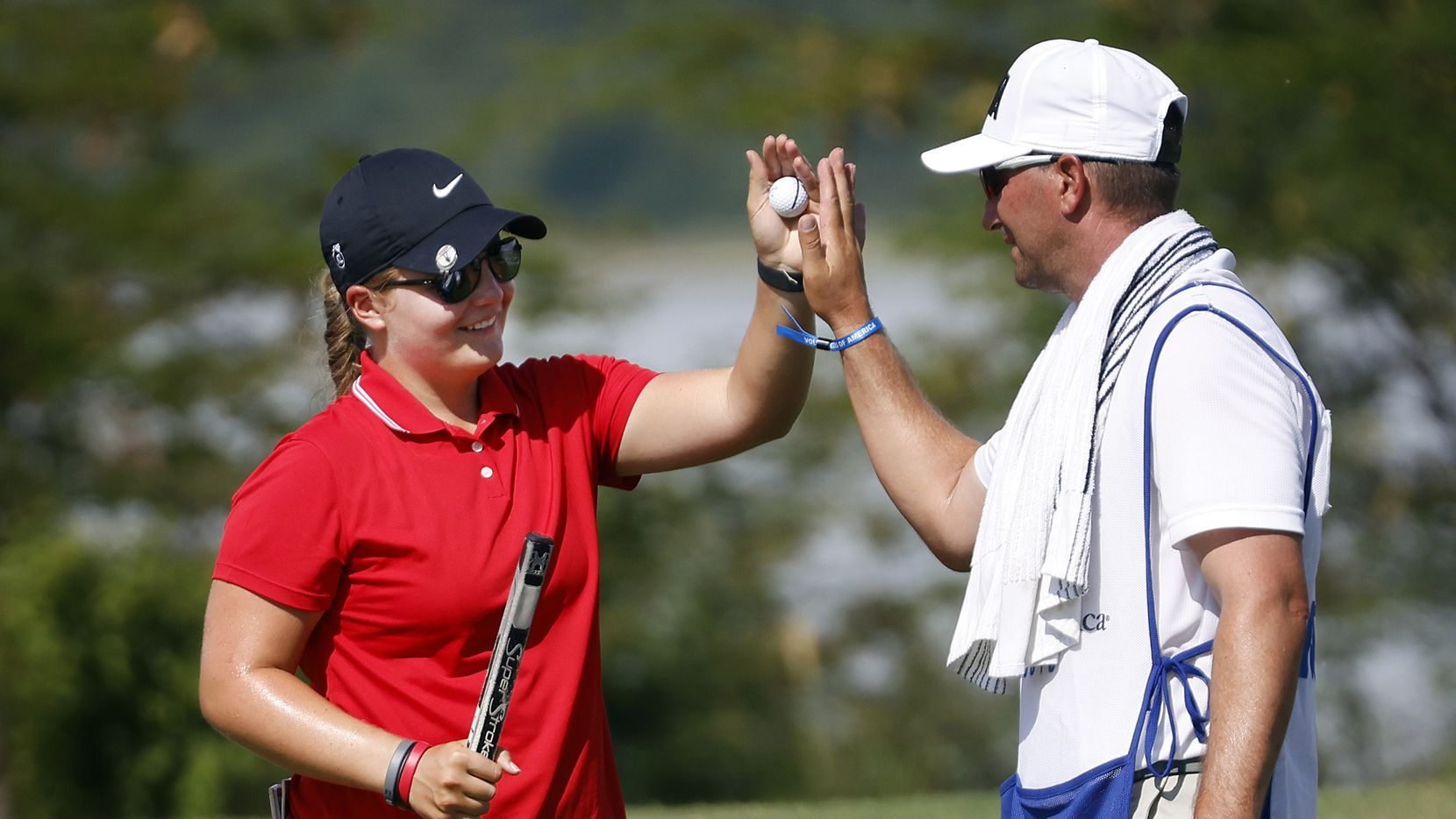 Amateur golfer Avery Zweig, 14, of McKinney (left) receives a high-five from her caddie Adam Golob after carding her first birdie of the LPGA VOA Classic at the Old American Golf Club in The Colony, Texas, Thursday, June 1, 2021. The putt came on No. 10 during the opening round.