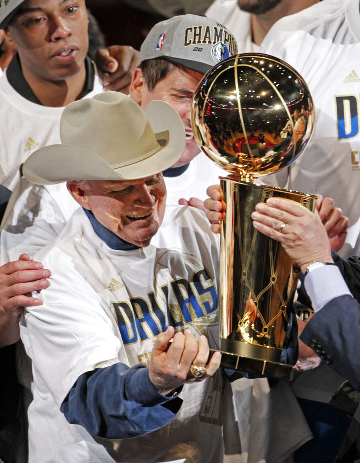 Dallas Mavericks original owner Don Carter (in cowboy hat) gets the Larry O'Brien NBA Championship trophy from NBA Commissioner David Stern as Dallas Mavericks owner Mark Cuban watches during the trophy presentation after game six of the NBA Finals between the Miami Heat and the Dallas Mavericks at the American Airlines Arena in Miami, Florida, June 12, 2011. Dallas Mavericks won 105-95.