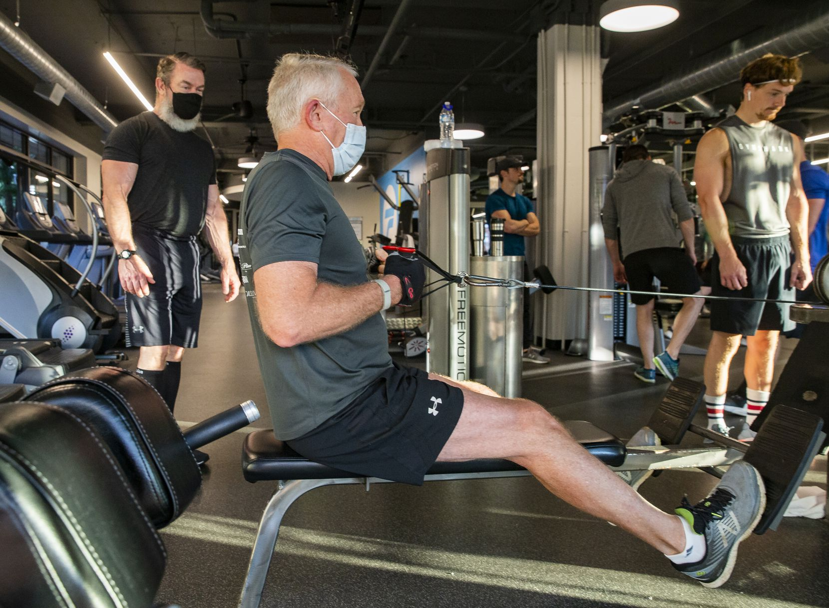Client Durward Watson of Oak Lawn (center) works out with Trophy Fitness trainer John Gordon (left) at the Uptown gym on May 18, 2020 in Dallas. Watson said he kept active by restoring landscaping and running while the gym was closed.