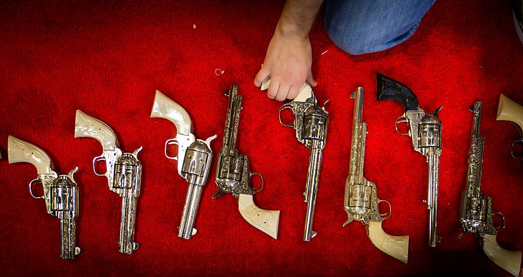 Workers at the Cimarron Firearms set up a display case with old west reproduction revolvers as exhibitors get set up for the opening of the NRA Annual Meetings and Exhibits at the Kay Bailey Hutchison Convention Center on Thursday, May 3, 2018, in Dallas. (Smiley N. Pool/The Dallas Morning News)
