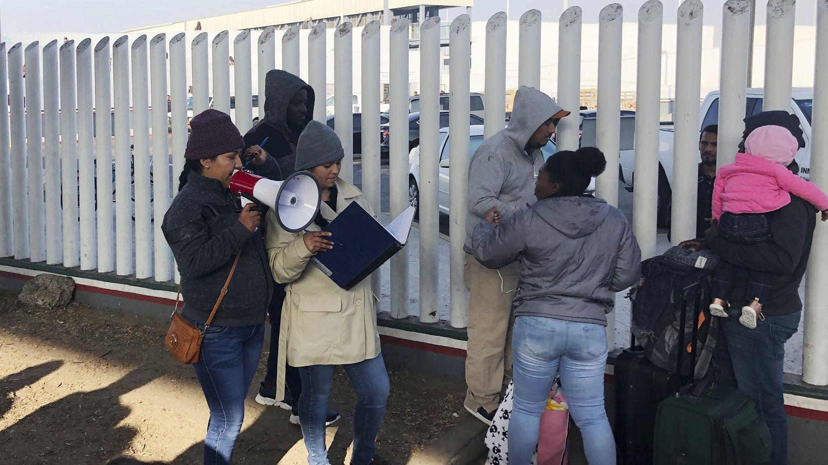 En esta fotografía del 12 de noviembre de 2019, voluntarios llaman por su nombre a personas que están en una lista de espera y que buscan conseguir asilo en Estados Unidos, en la ciudad de Tijuana, México, limítrofe con el territorio estadounidense.