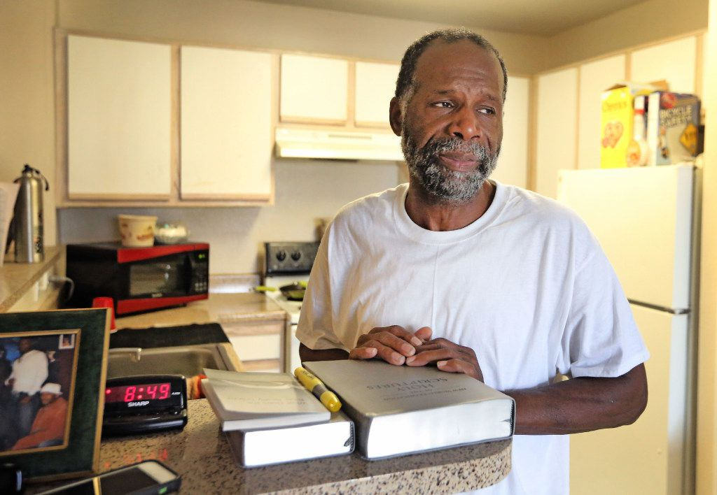 Harvey Pollard, with his Bibles, in his tidy Eban Village apartment