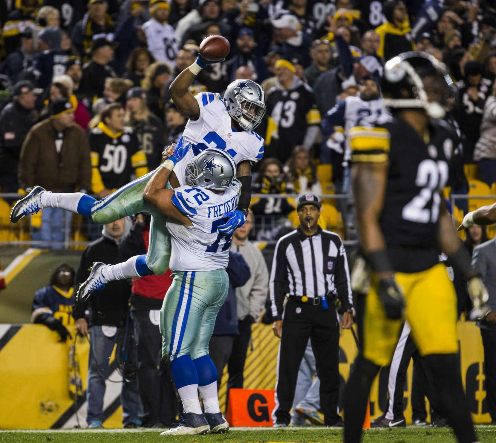 Dallas Cowboys running back Ezekiel Elliott (21) celebrates with center Travis Frederick (72) after running the ball to the end zone for the game winning touchdown during the fourth quarter of their game against the Pittsburgh Steelers on Sunday, November 13, 2016 at Heinz Field in Pittsburgh, Pennsylvania. Pittsburgh Steelers strong safety Robert Golden (21) is at right. The Cowboys won 35-30.