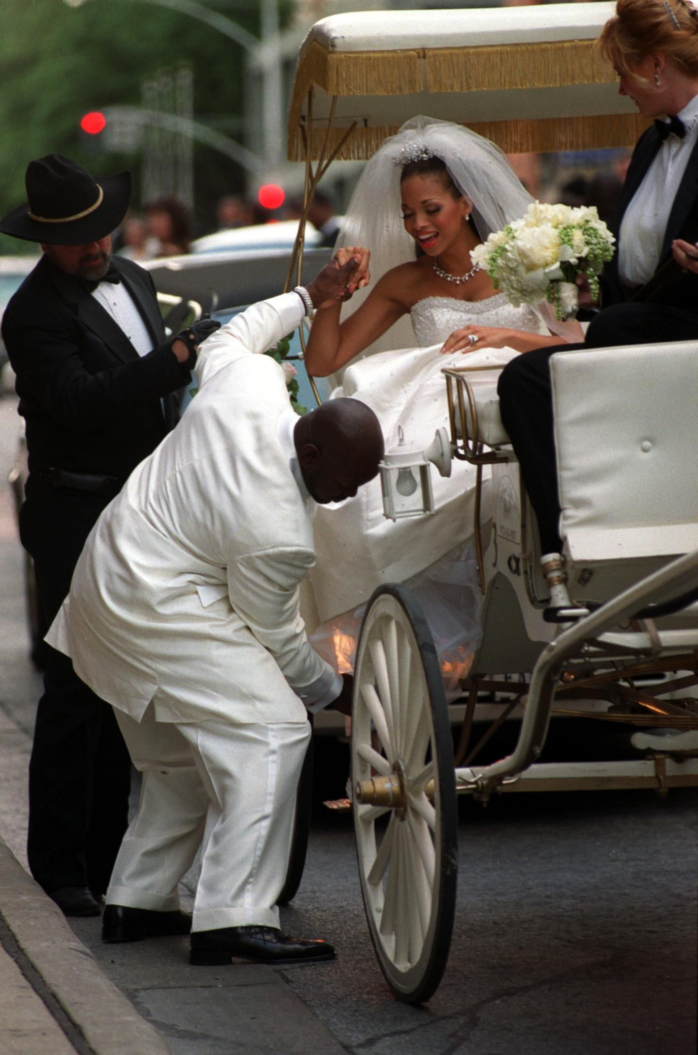 Emmitt Smith, running back for the Dallas Cowboys, and Pat Lawrence were married today. Emmitt Smith is shown helping his new wife from the carraige as they arrive at the Fairmont Hotel.