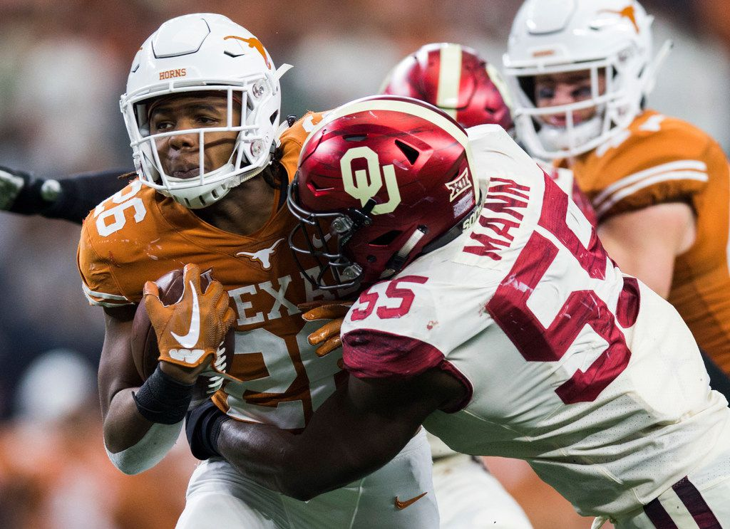Texas Longhorns running back Keaontay Ingram (26) is tackled by Oklahoma Sooners defensive lineman Kenneth Mann (55) during the fourth quarter of the Big 12 Championship football game between the Texas Longhorns and the Oklahoma Sooners on Saturday, December 1, 2018 at AT&T Stadium in Arlington, Texas. (Ashley Landis/The Dallas Morning News)