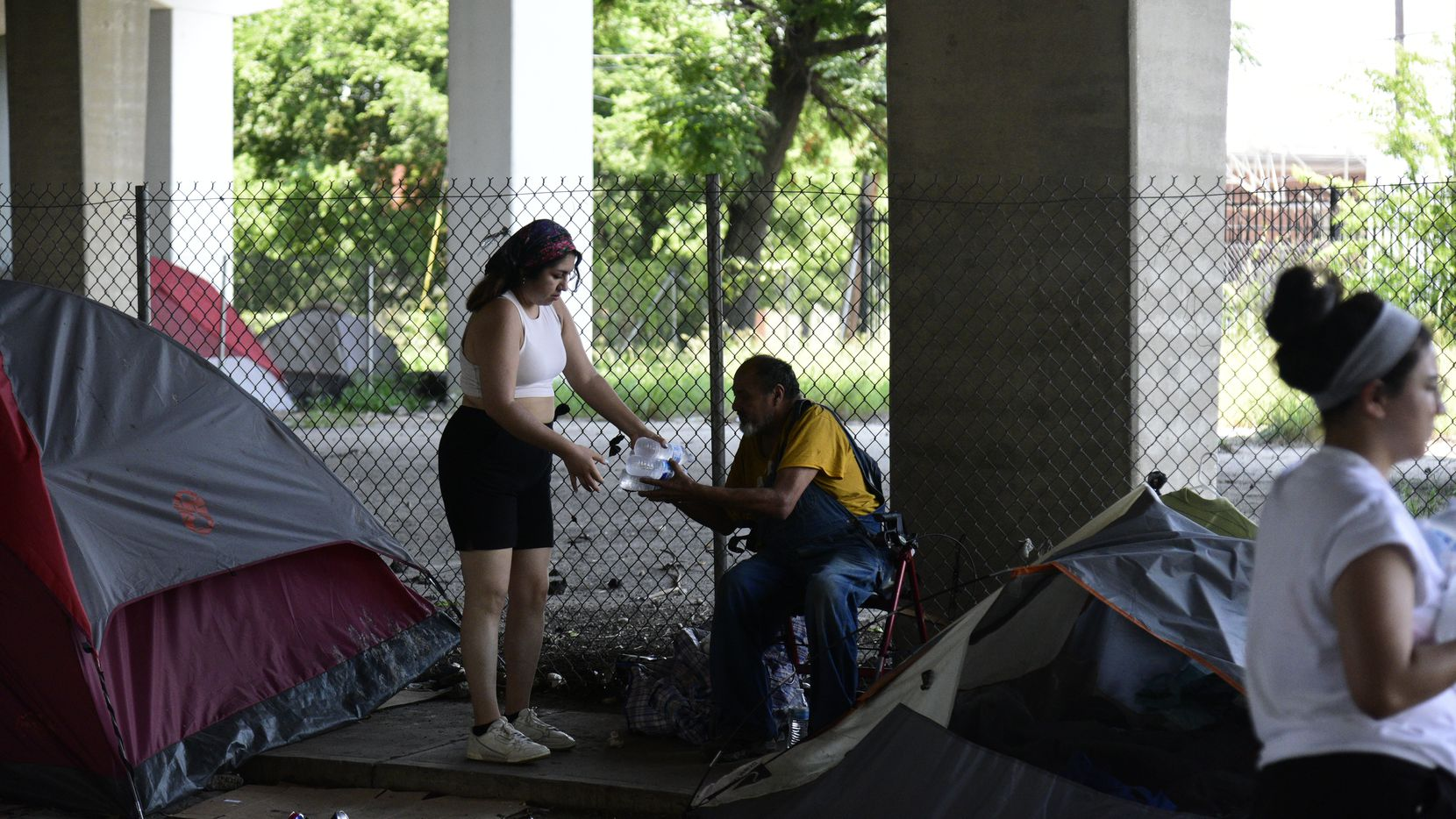 Volunteer Olivia Najera-Garcia hands out bottled water in under-freeway encampments for Feed the People Dallas on June 18, 2021.