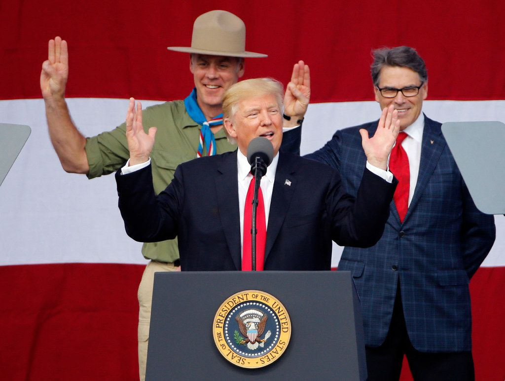 President Donald Trump joined former Boy Scouts, Interior Secretary Ryan Zinke, left, Energy Secretary Rick Perry, right, on stage at the 2017 National Boy Scout Jamboree at the Summit in Glen Jean, W.Va. (AP Photo/Steve Helber, File)