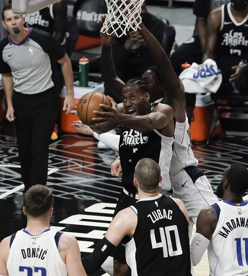 LA Clippers forward Kawhi Leonard (2) drives the the basket against Dallas Mavericks forward Dorian Finney-Smith (10) during the first half of an NBA basketball game at Staples Center on Saturday, May 22, 2021, in Los Angeles.