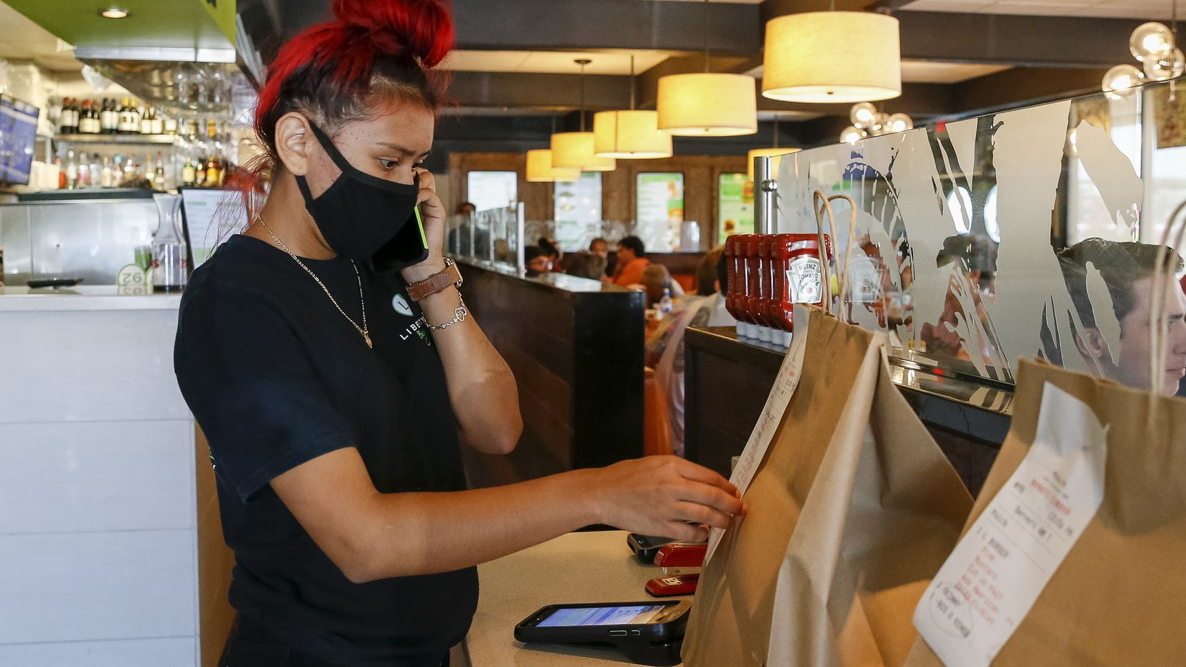 Liberty Burger employee Nicole Romero checks a to-go order while answering the phone at Liberty Burger in Dallas.
