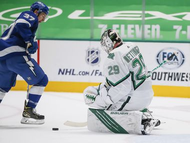 Dallas Stars goaltender Jake Oettinger (29) stops a shot from Tampa Bay Lightning forward Yanni Gourde (37) during the first period of an NHL hockey game in Dallas, Tuesday, March 16, 2021.