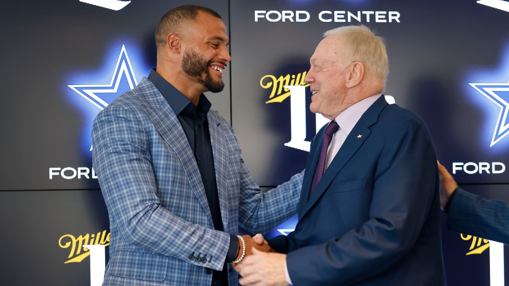 Dallas Cowboys quarterback Dak Prescott (left) and Dallas Cowboys owner Jerry Jones shake hands following a press conference at The Star in Frisco, Texas, Wednesday, March 10, 2021. Dak spoke about his freshly signed 4-year, $160 million contract with the team.