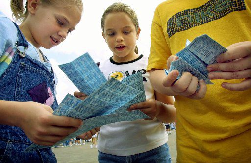 Corinne Pedersen, 10, Hannah Sifuentes, 9, and Preston Cooke, 13, count out their sheets of coupons at the State Fair of Texas in 2003. Here's the thing: They could still use those coupons this year. State Fair of Texas coupons don't expire.