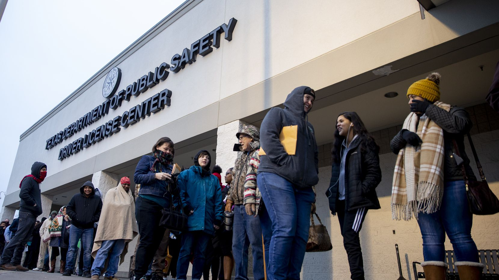 People line up outside the entrance at the Texas Department of Public Safety's driver's license mega-center in Garland.