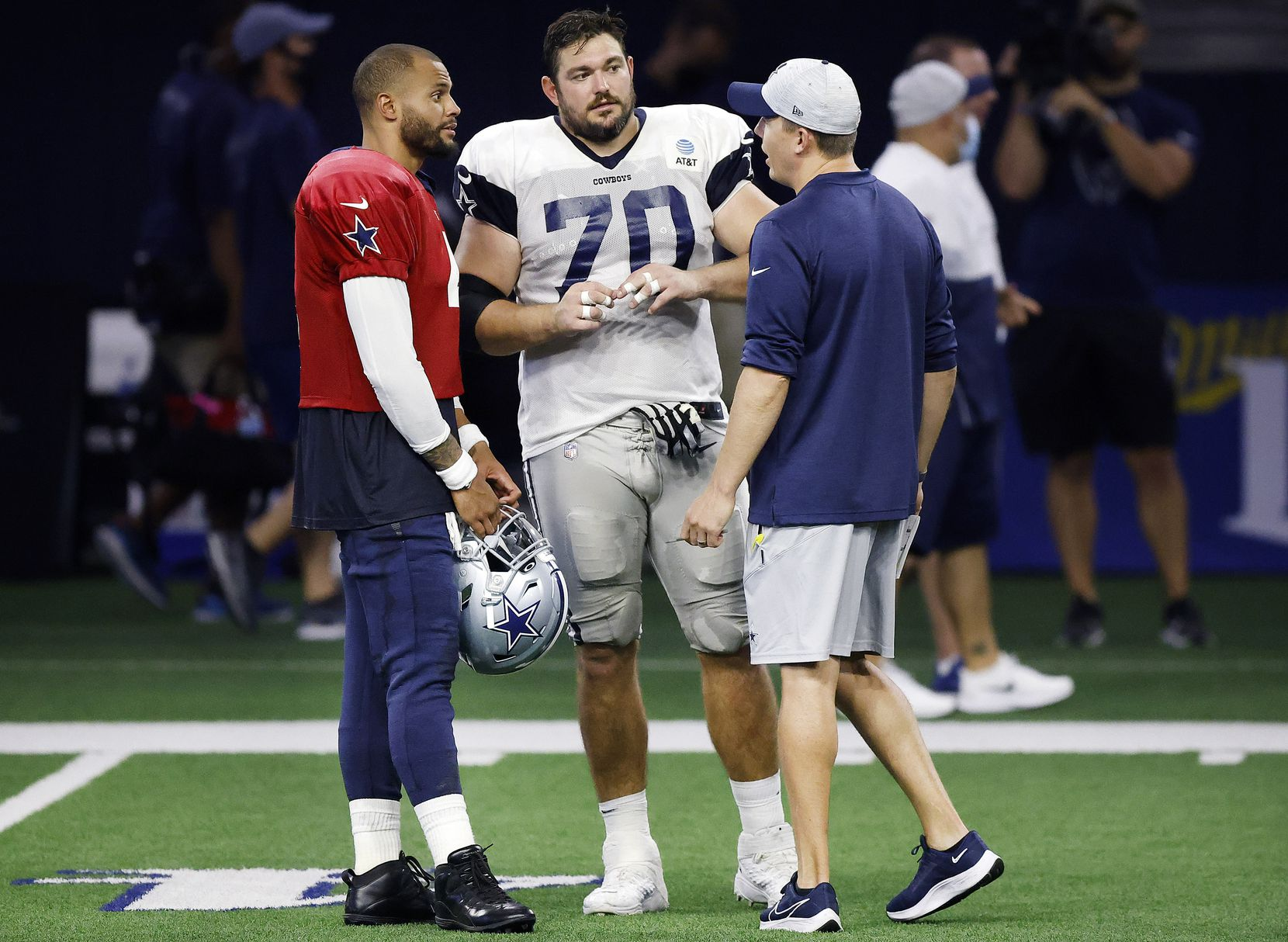 Dallas Cowboys guard Zack Martin (70) and quarterback Dak Prescott (4) visited with offensive coordinator Kellen Moore during training camp practice at The Star in Frisco on Aug. 27, 2021.