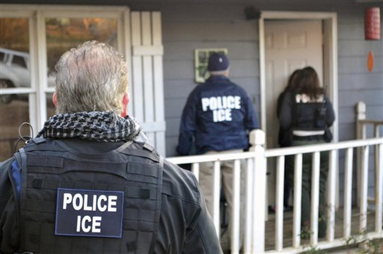 En esta fotografía del 9 de febrero de 2017, facilitada por el Servicio de Control de Inmigración y Aduanas de Estados Unidos (ICE por sus siglas en inglés), varios agentes de esa agencia llegan a una vivienda en Atlanta dentro de una operación para detener a prófugos de inmigración, personas que regresaron al país tras su deportación y extranjeros delincuentes en general. (AP/BRYAN COX)