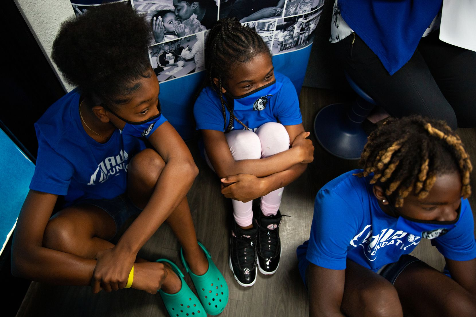 Kristian Haynes, 13, Dameah Settles, 11, and Derrick Washington, 13 listen to Dallas Mavericks guard Nate Hinton talk about the Mavs Foundation's of its newest reading and earning center renovation at the Moorland YMCA at Oak Cliff on August 3, 2021. (Shelby Tauber / Special Contributor)