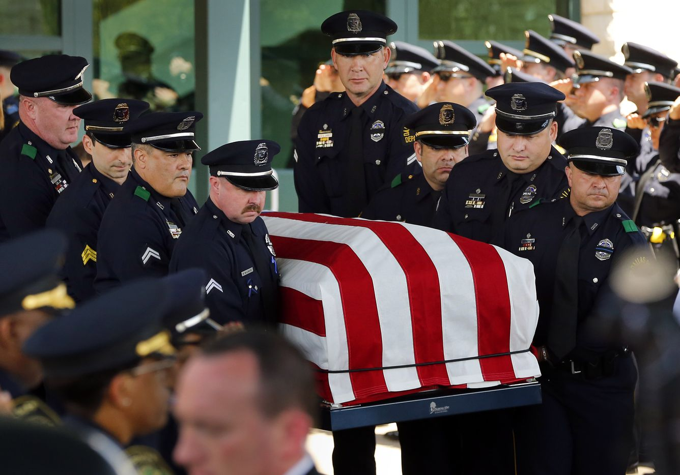 Police pallbearers carry the flag draped casket of fallen Dallas police officer Lorne Ahrens from Prestonwood Baptist Church in Plano, Wednesday, July 12, 2016.