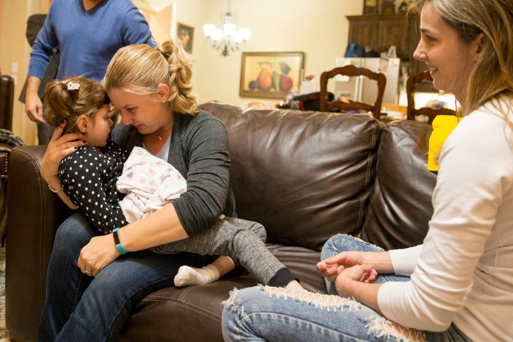 Penny Howard has an intimate moment with Anny Fishcher, 8, of Brasília, Brazil, who suffers CDKL5, a rare genetic disorder, as Fischer's mother, Katiele Fischer (right) looks on at the Howard family home on Oct. 20, 2016 in The Colony, Texas. Both families connected though social media, due to their common experience using hemp oil to ease the seizures of their CDKL5 suffering daughters. (Ting Shen/The Dallas Morning News)
