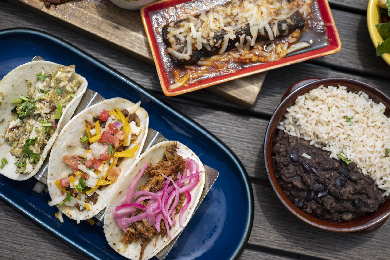 Tacos with chicken verde, ground beef chorizo and pulled pork, with a three chili sauce cheese enchilada, along with a bowl of smokey black beans and lime coconut rice, from the Mother's Day brunch menu from Blue Mesa Grill in Dallas.