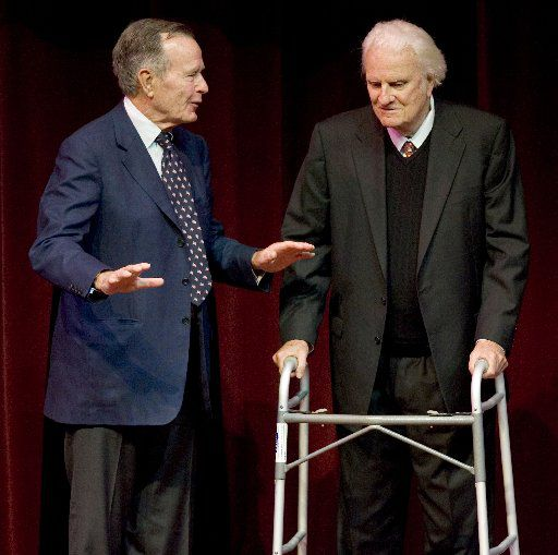 Former President George Bush talks with the Rev. Billy Graham as he presents the evangelist the George Bush Award for Excellence in Public Service on April 10, 2006, in College Station