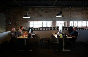 Matt Tschoegl (left) and Logan Fisher, full-stack developers for ParkHub, work at the company's Deep Ellumoffice. (Rose Baca/The Dallas Morning News)
