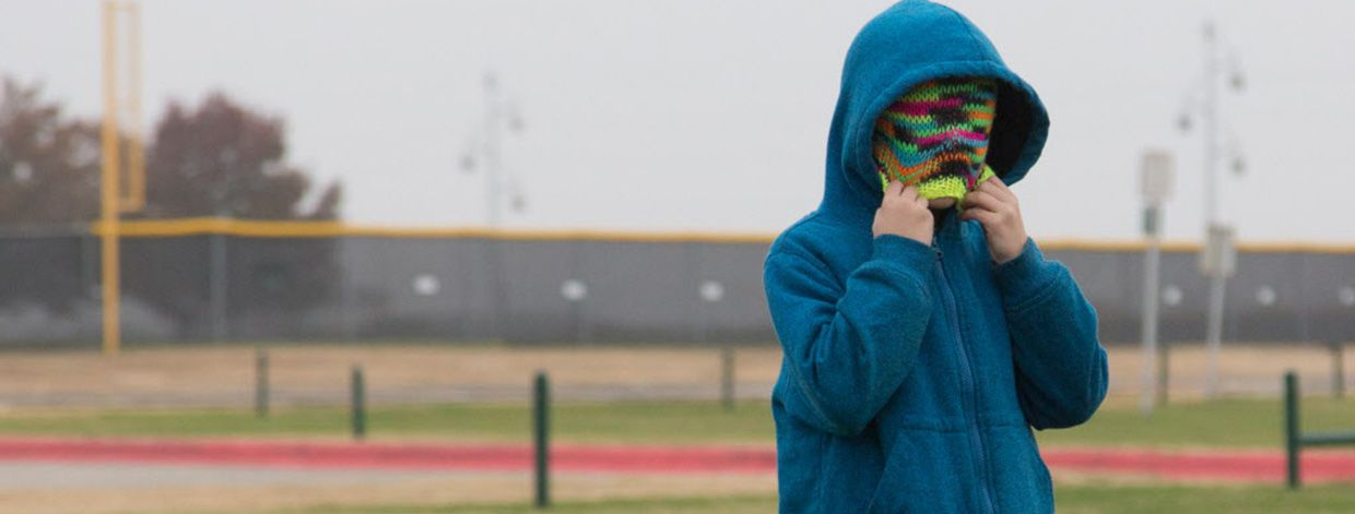 Colin Stokes covers his face with his beanie to keep warm while he plays soccer with other home-schooled children Thursday at North Lakes Park in Denton.