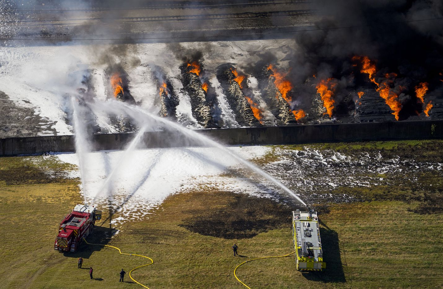 Aerial view of fire crews working at the site of a massive blaze in an industrial area on Wednesday, Aug. 19, 2020 in of Grand Prairie, Texas. The fire in the 2000 block of West Marshall Drive, near the Bush Turnpike. Among the businesses in the area is Poly-America, a company that produces trash bags and other plastic products.