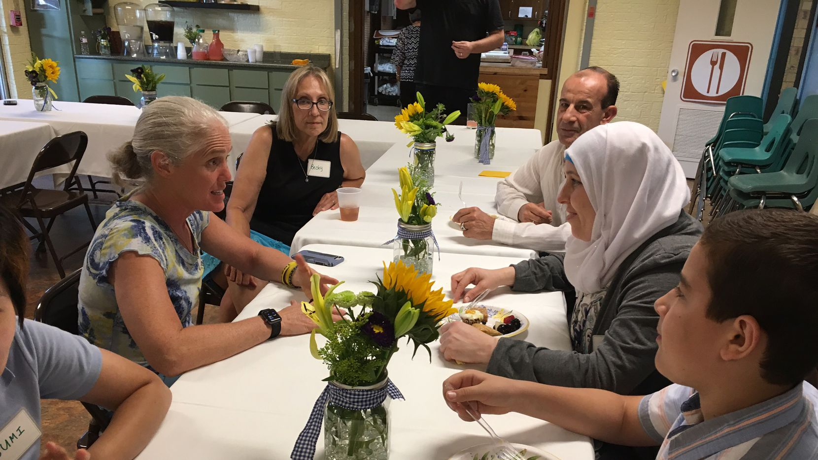 Members of the Arapaho United Methodist Church congregation share a meal with the Fajer family.