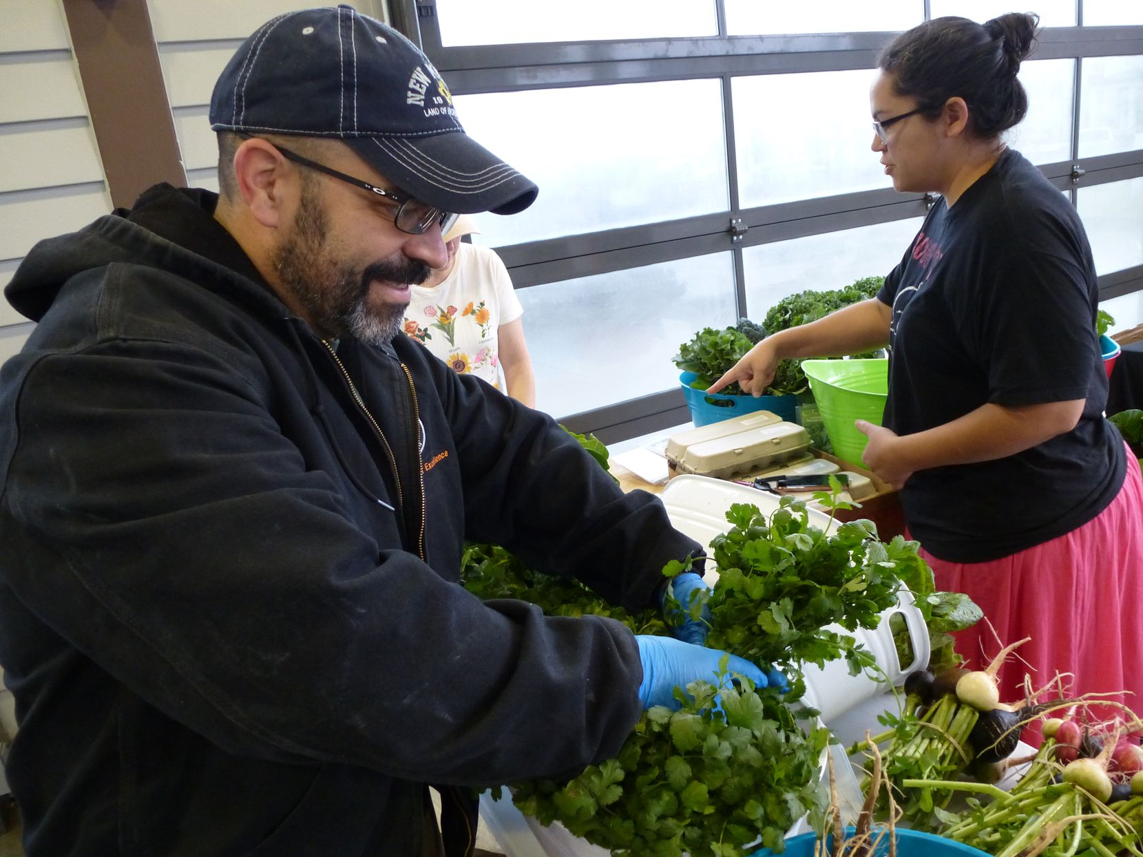 """At Coppell Farmers Market, farmer Russell Gonzales sorts through cilantro from his Delanco Farm in Paradise. He wears blue safety gloves handed out by the market manager """"just to give people peace of mind."""""""