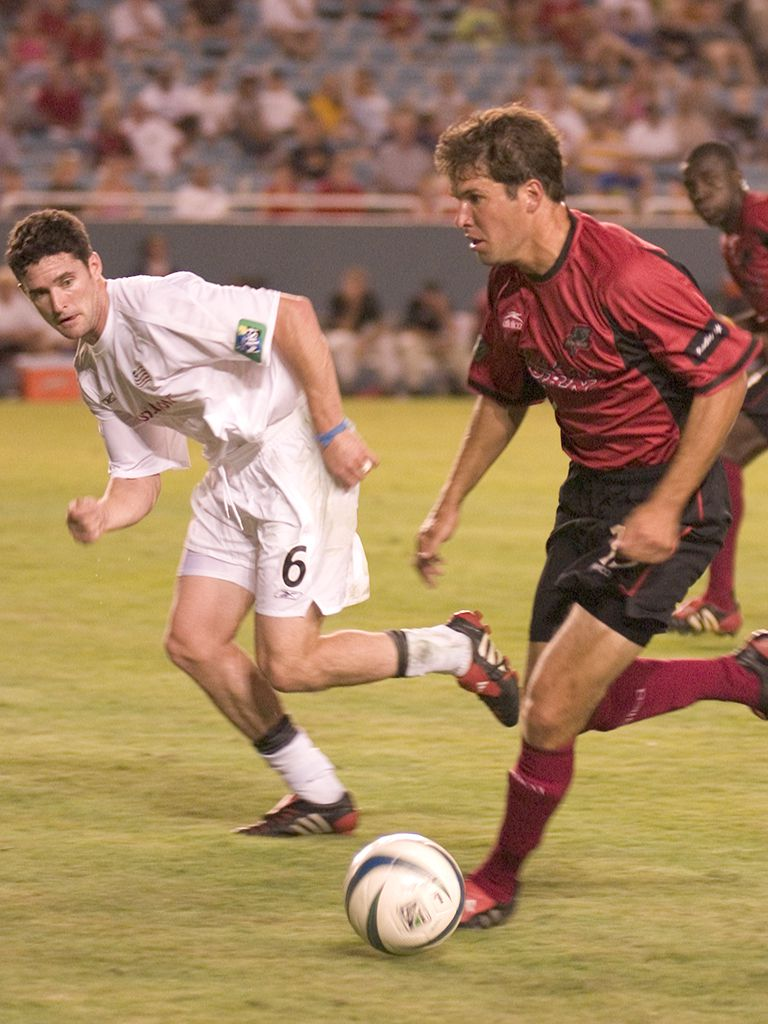 Eric Quill playing for the Dallas Burn in 2004 attempting to dribble past Jay Heaps of the New England Revolution