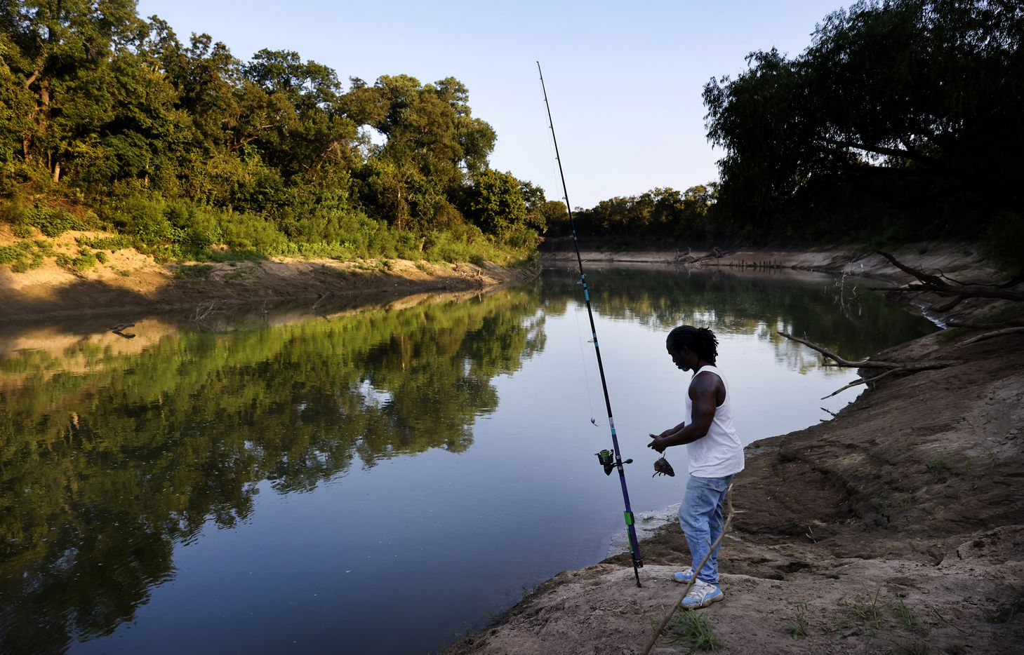 As the sun fades on the Trinity River, Odell Allen attaches a carp head to his hook as he fishes for alligator gar near the Great Trinity Forest Way bridge in Dallas, Wednesday evening, September 1, 2021.  (Tom Fox/The Dallas Morning News)