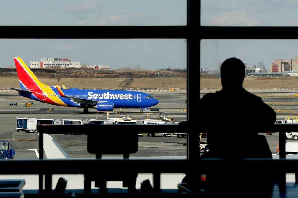 In this Jan. 25, 2019, file photo a Southwest Airlines jet moves on the runway as a person eats at a terminal restaurant at LaGuardia Airport in New York.