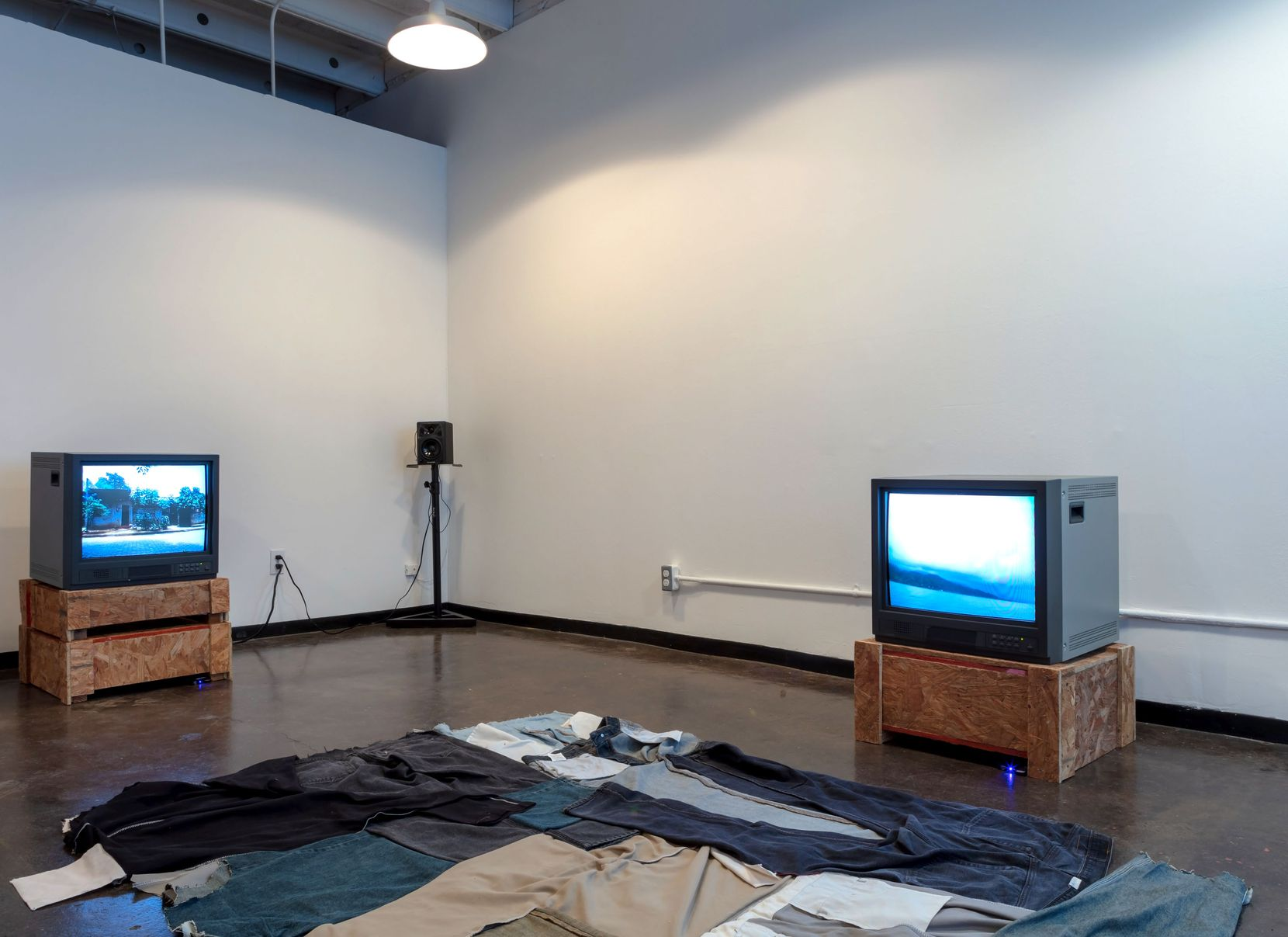 "Installation by artist Francis Almendárez at ""The Potential Wanderer,"" curated by Caroline Elbaor, at the Reading Room in Dallas.  On the floor is a large blanket made of several pairs of pants."