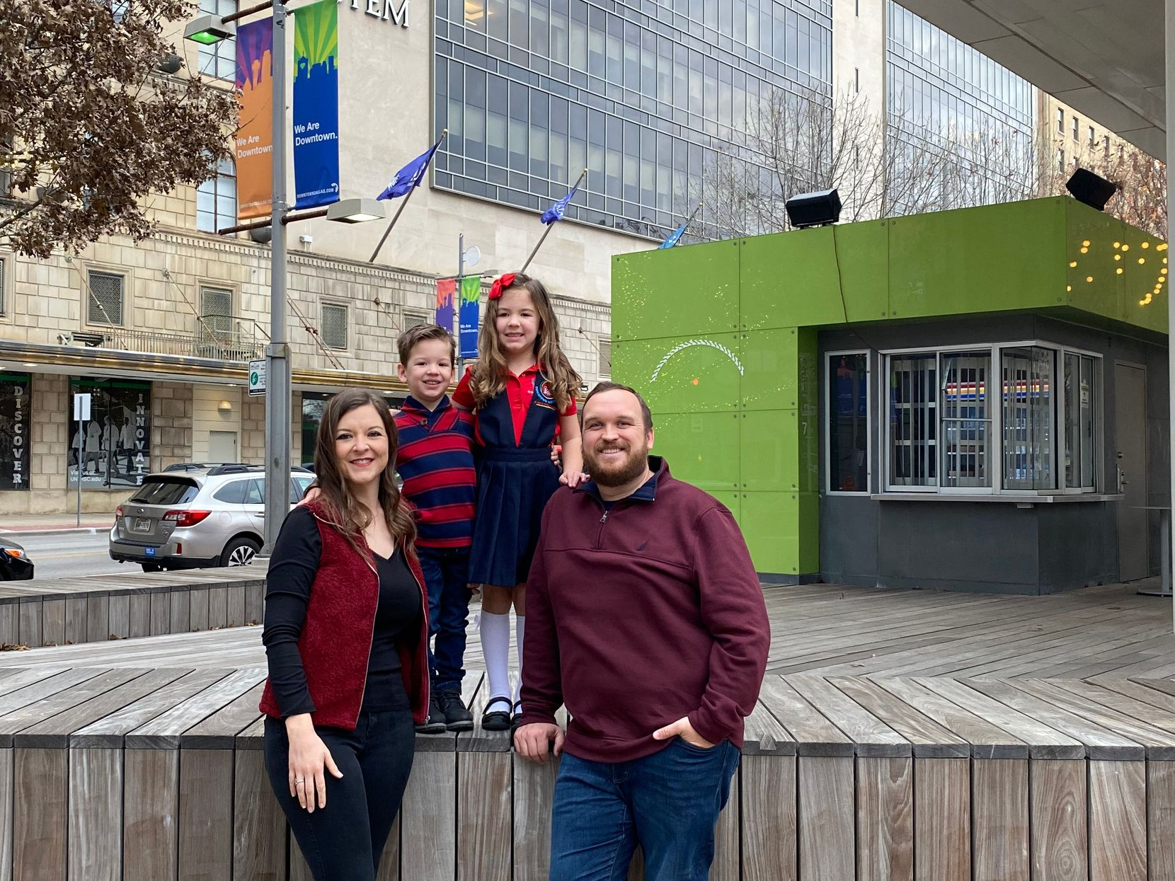Parents Elizabeth and Chad Thorpe with their 3-year-old son Garrett and 6-year-old daughter Landry, wearing her school uniform, across the street from the Downtown Montessori at Ida B. Wells Academy. Landry is among the first class of kindergartners at the new school.