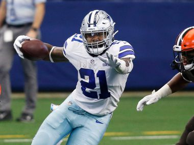 FILE -- Cowboys running back Ezekiel Elliott (21) tries to evade Browns defenders during the second quarter of play at AT&T Stadium in Arlington on Sunday, Oct. 4, 2020.