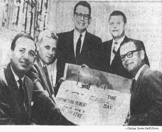 """A group of Dallas D-Day veterans, including DMN photographer John Flynn at lower right, huddle around a paper advertising the film """"The Longest Day."""" Photograph published in The Dallas Morning News on Oct. 19, 1962."""