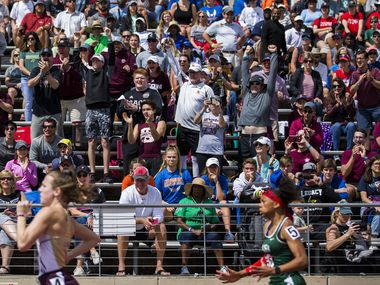 People watch as 5A girls 100 meter dash competitors sprint by during the TAPPS State Championship Track and Field meet at Panther Stadium in Hewitt, Texas on Saturday, May 4, 2019.